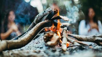 zwei Leute sitzen am Lagerfeuer