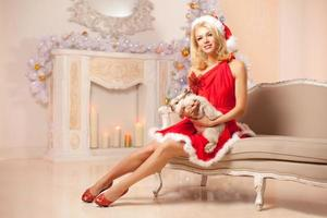 junge schöne lächelnde Weihnachtsfrau nahe dem Weihnachtsbaum mit foto