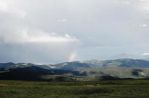 Rasenfläche mit Bergen und einem Regenbogen in der Ferne