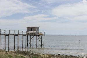 Schuppen auf Dock über Wasser mit bewölktem blauem Himmel