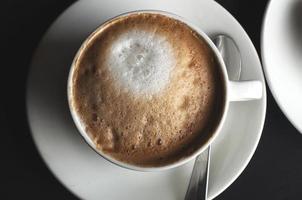 weiße keramische Kaffeetasse gefüllt mit einem Cappuccino