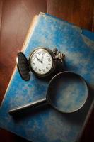 Lupe und Taschenuhr auf antikem Buch. foto