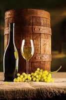 Weinzusammensetzung altes Fass mit Weinglasflasche und Weintraube foto