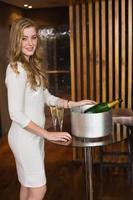 hübsche Blondine, die mit Champagner in die Kamera lächelt foto