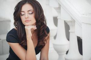 Porträt einer Frau, die auf Stufen in der Stadt sitzt foto