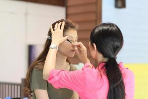 Nahaufnahmefrau, die Make-up durch Künstler angewendet hat foto