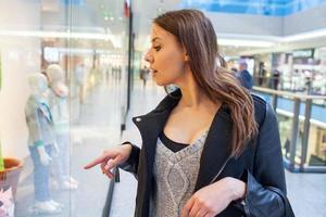 Foto der jungen freudigen Frau mit Handtasche auf dem Hintergrund
