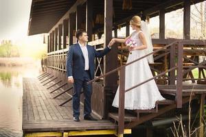Braut und hübscher Bräutigam gehen die Treppe am Pier hinunter