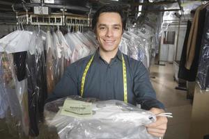 selbstbewusster Besitzer, der chemisch gereinigte Kleidung in Wäsche gibt foto