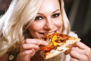 attraktives blondes Mädchen, das Pizza isst foto