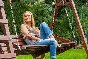 sinnliche blonde Frau, die im Park auf Holzbank sitzt. draussen foto