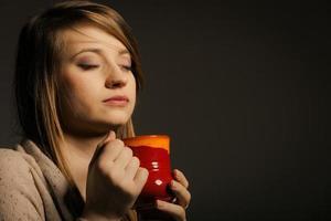 hübsche Frau, die träumt, während sie eine Tee-Tasse hält