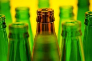 zehn leere Bierflaschen auf gelbem Grund foto