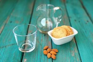 leeres Glas mit hausgemachten Mandelkeksen und ganzen Mandeln foto