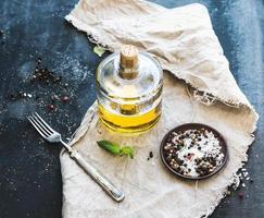 Flasche Olivenöl mit frischem Basilikum und Gewürzen darüber foto