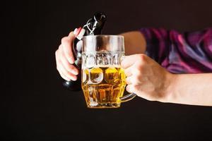 junger Mann, der Bier von der Flasche in den Becher gießt foto