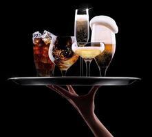 Hand hält ein Tablett mit verschiedenen alkoholischen Getränken hoch