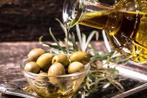 Olivenöl und Oliven auf Holztisch foto