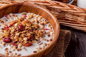hausgemachtes Müsli mit Milch, Beeren, Samen und Nüssen foto