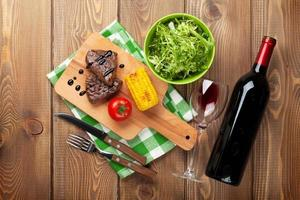 Steak mit gegrilltem Mais, Salat und Rotwein foto