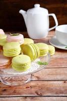 Makrone auf einem Ständer mit Teekanne und Tasse