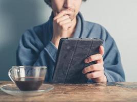 Mann im Bademantel, der Kaffee trinkt und Tablette benutzt foto