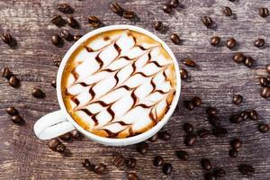 Tasse Kaffee und geröstete Bohne auf altem Holztisch