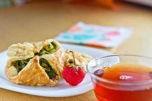 frisch gebackene hausgemachte Blätterteigkuchen mit einer Tasse Tee foto
