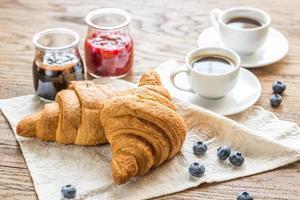 Croissants mit frischer Blaubeere und zwei Tassen Kaffee foto