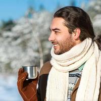 junger Mann mit Tee, der im verschneiten Wald steht foto