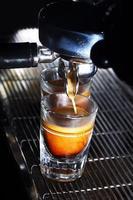 Espressomaschine, die einen Kaffee brüht. Kaffee fließt in Schnapsgläser foto