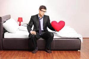 hansome junger Mann, der ein rotes Herz hält, das auf Bett sitzt foto