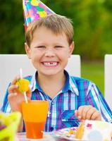 glücklicher Junge, der Spaß an der Geburtstagsfeier hat foto