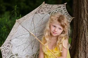 kleines Mädchen, das Sonnenschirm hält
