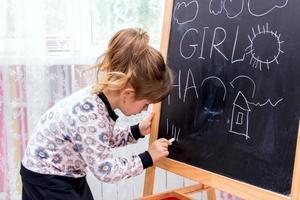 kleines schönes Mädchen, das auf einer Tafel zeichnet.