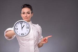 Porträt des netten Mädchens, das große Uhr in ihren Händen hält foto