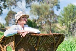 Frau sitzt auf einer Bank im Garten foto