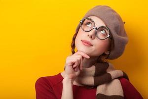 rothaariges Mädchen in den Gläsern und im Schal auf gelbem Hintergrund.