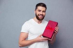 lächelnder lässiger Mann, der Geschenkbox hält