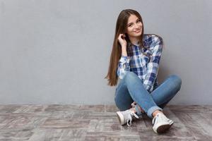 glückliche Frau, die auf dem Boden sitzt foto