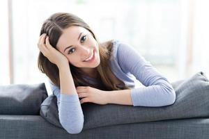 Frau sitzt auf dem Sofa foto