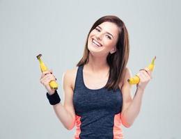 glückliche sportliche Frau, die Bananen hält foto