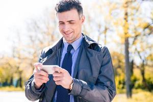 glücklicher Geschäftsmann mit Smartphone foto