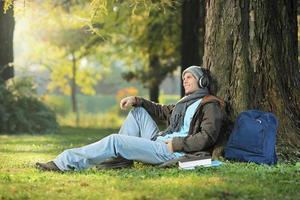 männlicher Student, der sich entspannt und Musik hört, die im Park sitzt foto