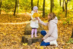 glückliche Familienmutter und kleine Tochter, die auf Herbstspaziergang spielen foto