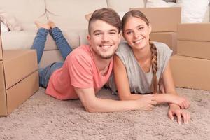 angenehmes Paar auf dem Boden liegen foto
