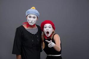 Porträt des traurigen Pantomimenpaares, das lokal auf grauem Hintergrund weint foto