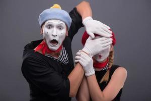 Porträt des traurigen Pantomimenpaares, das lokal auf grauem Hintergrund weint