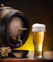 Bierfass mit einem Glas Bier auf Holztisch foto
