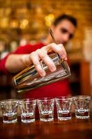 Nahaufnahme des Barmanns, der alkoholisches Getränk und Cocktails einschenkt foto